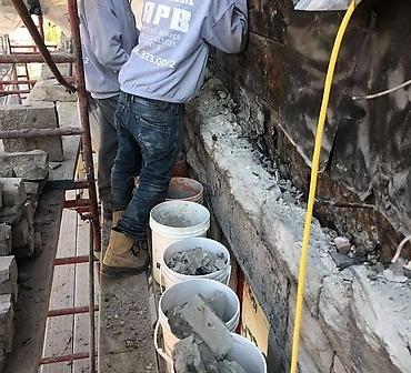 Reparation mur de pierre St-Marc Montreal - Pierre naturelle à l'époque souvent installée directement sur la structure de bois (carré de bois) qui cause des problèmes d'infiltrations d'eau et dégradation de la structure à long terme.