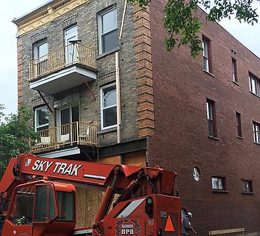 Reconstruction complete d'un mur de briques sur la rue Aylwin a Montreal - Reconstruction complète du mur de briques. Allèges de pierres naturelles grises St-Marc. Briques Louisiana de Meridian Brick.